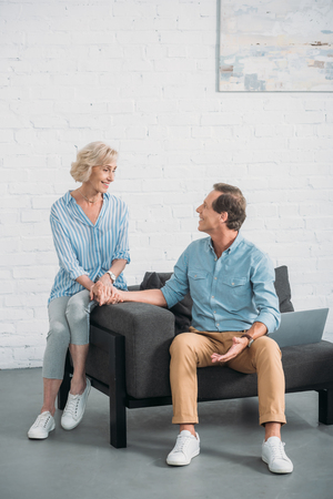 happy senior couple holding hands and smiling each other while sitting together at home