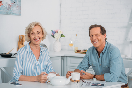 happy senior couple smiling at camera while drinking tea together at home
