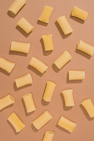 top view of pasta spilled on beige surface