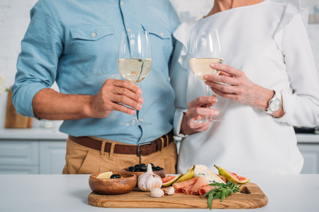 cropped shot if elderly couple holding glasses of wine while eating delicious snacks at home