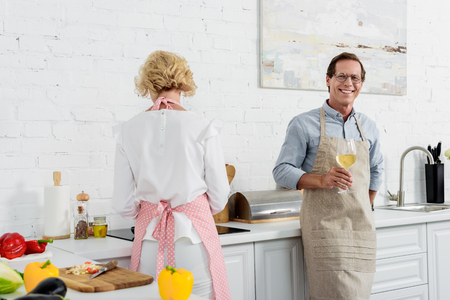 elderly man in apron holding glass of wine and smiling at camera while cooking with wife in kitchen Stock Photo