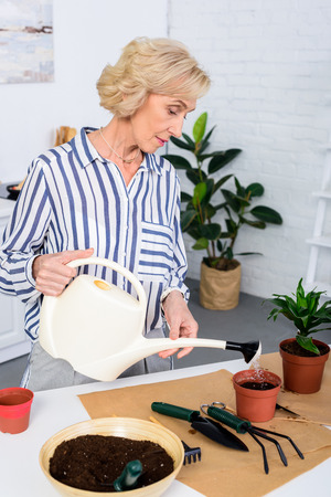 beautiful senior woman watering soil with watering can at home Stock Photo