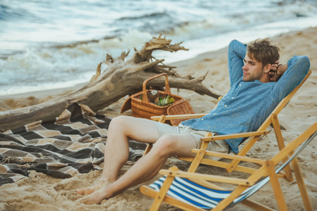 side view of young man resting in beach chair on sandy beach