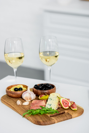 close-up view of glasses of wine and delicious snacks on wooden board on table