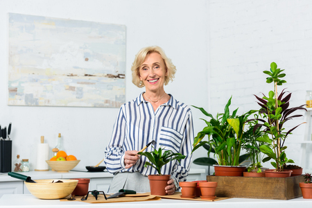happy senior woman smiling at camera while cultivating potted plants at home