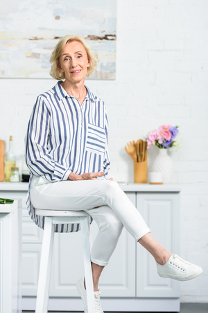 attractive grey hair woman sitting on high chair in kitchen and looking at camera