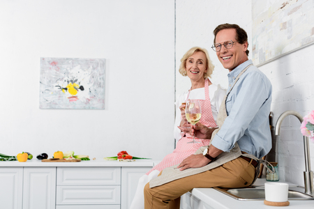 happy elderly couple in aprons holding glasses of wine and smiling at camera in kitchen Stock Photo