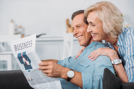 side view of smiling elderly couple reading business newspaper at home