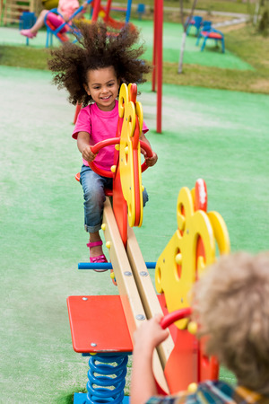 happy curly african american child riding on rocking horse with boy at playground Stock Photo