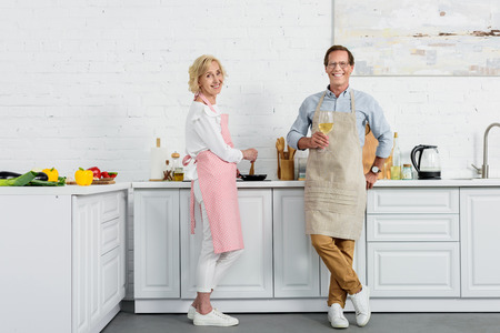 happy senior couple in aprons smiling at camera while drinking wine and cooking in kitchen Stock Photo
