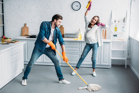 couple in rubber gloves having fun with mop during cleaning kitchen