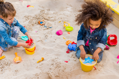 high angle view of two little multicultural children using plastic molds in sandbox at playground Фото со стока - 106026541