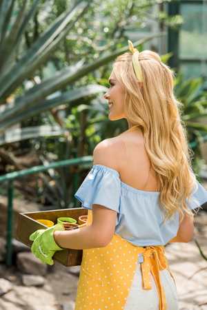 back view of smiling blonde woman holding box with flower pots in greenhouse 版權商用圖片