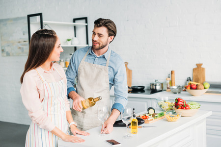 boyfriend pouring wine into glass and looking at girlfriend in kitchen