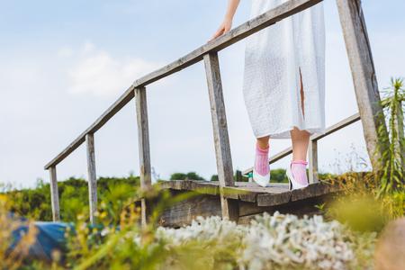 low section of girl in white dress walking on wooden footbridge