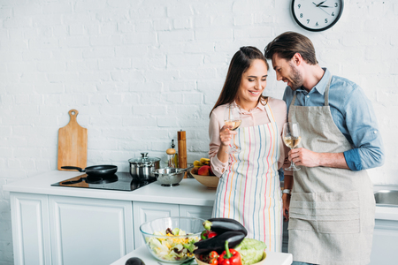 smiling couple standing with glasses of wine in kitchen
