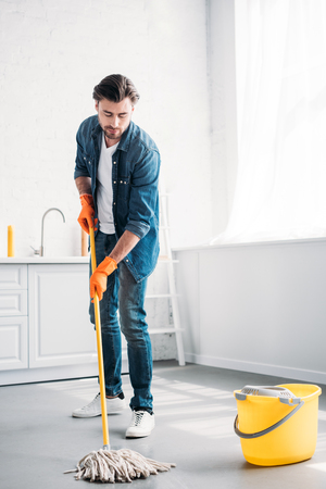handsome man cleaning floor in kitchen with mop Stock Photo