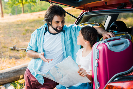 father and daughter looking at each other and holding map at car trunk