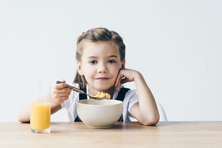 smiling little schoolgirl eating healthy breakfast isolated on white Zdjęcie Seryjne