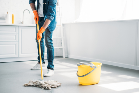 immagine ritagliata dell'uomo che pulisce il pavimento in cucina con il mop Archivio Fotografico