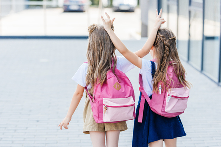 rear view of little schoolgirls making horns gesture to each other on street
