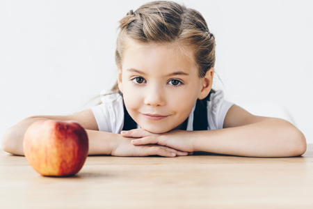 little schoolgirl sitting at table with red apple looking at camera isolated on white