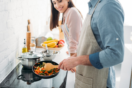 cropped image of boyfriend frying vegetables on electric stove in kitchen