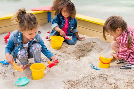 trzy wieloetniczne małe dzieci bawiące się plastikowymi łyżeczkami i wiaderkami w piaskownicy na placu zabaw