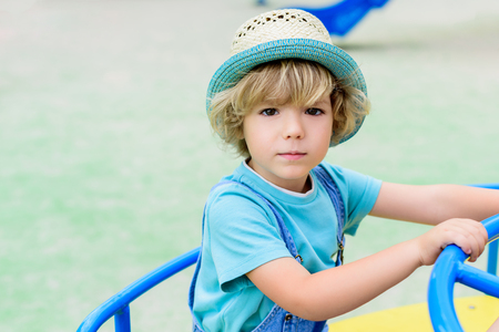 selective focus of adorable little boy in panama riding on carousel at playground 免版税图像