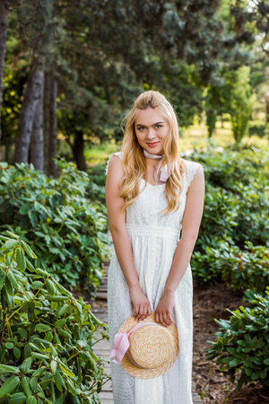 beautiful young blonde woman in white dress holding wicker hat and smiling at camera in park Banco de Imagens
