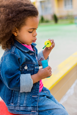 side view of curly african american little child playing with soap bubbles