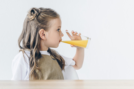 cute little schoolgirl with drinking orange juice isolated on white