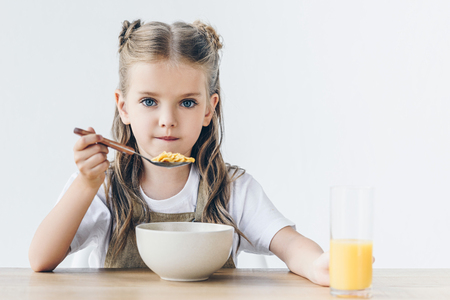 little schoolgirl eating healthy breakfast isolated on white and looking at camera Stock Photo