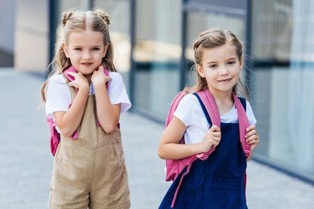 adorable little schoolgirls with pink backpacks walking on street Reklamní fotografie