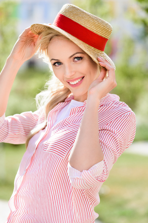 portrait of smiling young woman in straw hat on blurred background Stock fotó