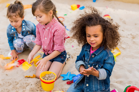 selective focus of curly african american child playing wit friends in sandbox at playground