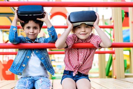 adorable little children taking off virtual reality headsets at playground Stock fotó