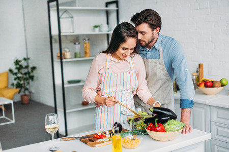 girlfriend cooking and mixing salad in kitchen and boyfriend hugging her
