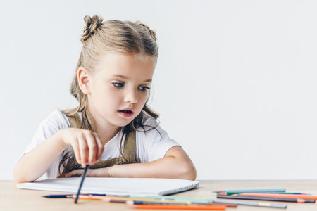 adorable little schoolgirl drawing with color pencils isolated on white Banque d'images - 105973874