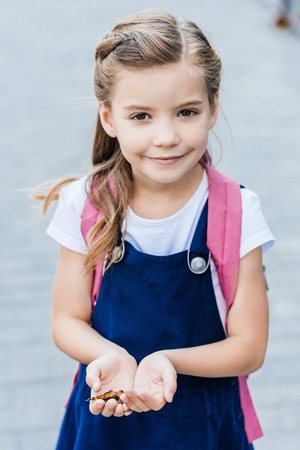 adorable little schoolgirl holding butterfly in hands and looking at camera