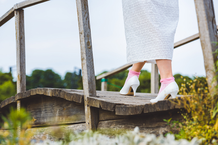 cropped shot of woman in white dress walking on wooden footbridge