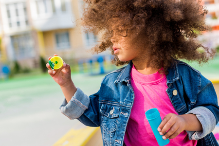 curly african american little child playing with soap bubbles