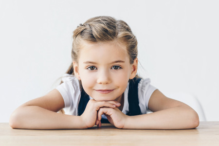 smiling little schoolgirl leaning on table and looking at camera isolated on white
