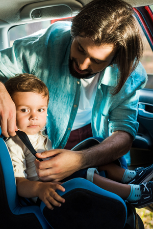 father fastening adorable son in safety seat in car