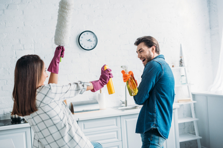 happy couple having fun during cleaning kitchen and fighting with cleaning tools