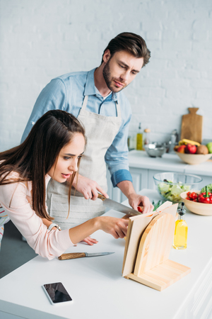 boyfriend cutting vegetables and girlfriend reading recipe in kitchen Stock Photo