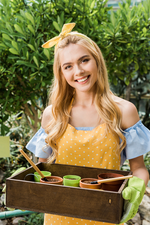 beautiful young female gardener holding box with flower pots and smiling at camera