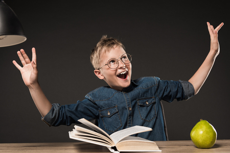 excited school boy in eyeglasses gesturing by hands while reading book at table with lamp and pear on grey background 免版税图像