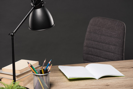selective focus of lamp, colour pencils, stack of books, plant and empty textbook on table on grey background