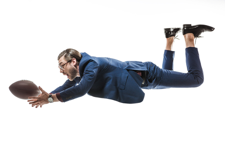 side view of businessman catching rugby ball while falling isolated on white Stock Photo